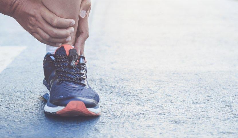 Fotografi på en löpares sko med händer som håller runt vristen