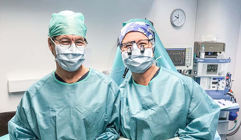 Kirurger i full mundering tittar in i kameran